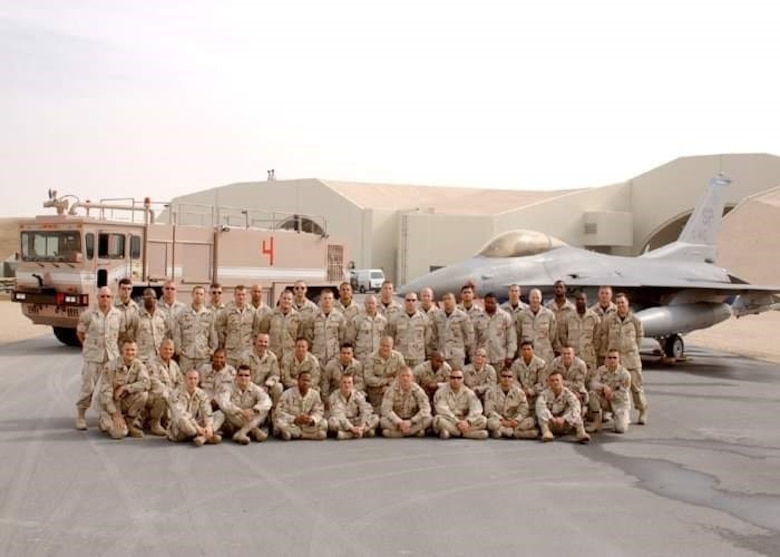 Then U.S. Air Force Master Sgt. John Thompson and other deployed firefighters take a group photo at Al Udeid Air Base, Qatar, sometime between Dec. 2002 to July 2003.