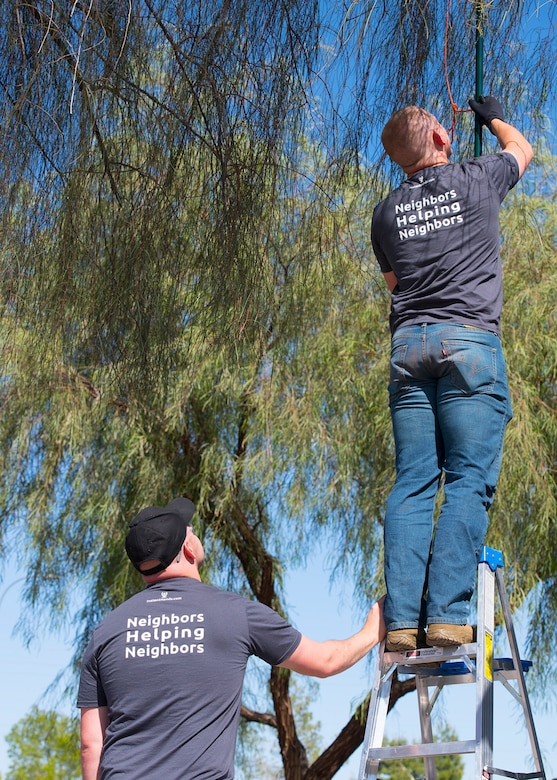 Airman 1st Class Bradley Chitwood, 56th Force Support Squadron food service journeyman (left), and Senior Airman Montana McCormick, 56th Force Support Squadron lead recreational specialist, trim a tree April 1, 2020, in Avondale, Ariz.