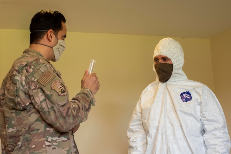 Tech. Sgt. Matthew Borquez, 100th Civil Engineer Squadron emergency management logistics noncommissioned officer in charge, instructs a Team Mildenhall Airman on the proper amount of household bleach needed to create a cleaning solution at RAF Mildenhall, England, April 15, 2020. Cleaning-team members use chemicals that would destroy any potential Coronavirus remaining on common surfaces. (U.S. Air Force photo by Airman 1st Class Joseph Barron)