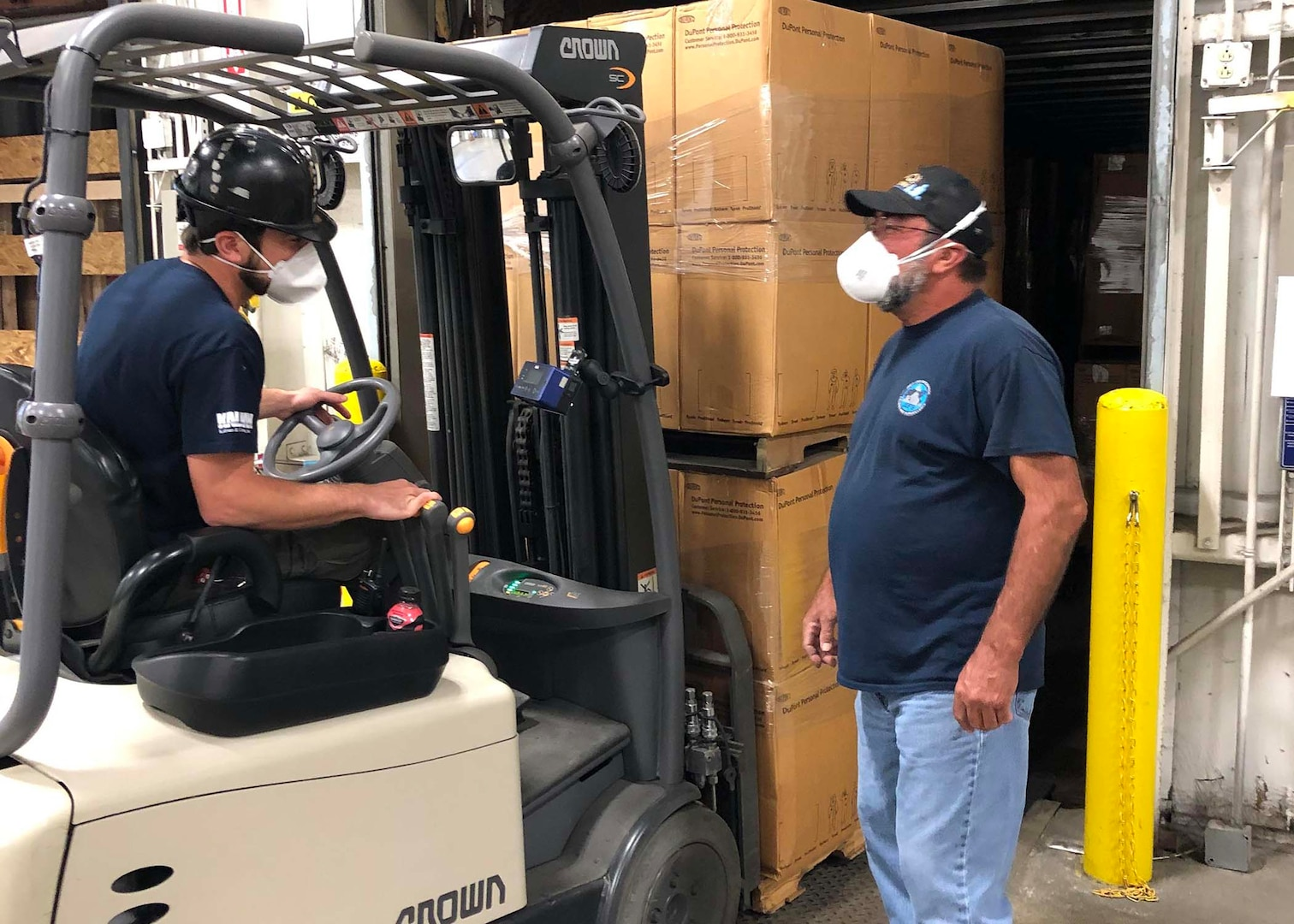 Andy McElroy, a transportation driver at Marine Corps Logistics Command, helps Shipping and Receiving Technician Christopher Leymeister (seated on forklift) with the loading of personal protective suits the command provided to the Defense Logistics Agency as part of their effort to gather supplies for the COVID-19 response.
