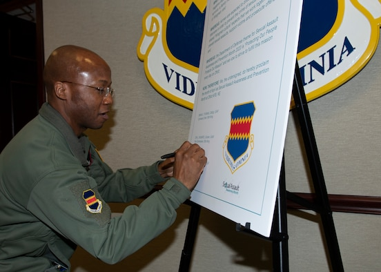A photo of a man signing a large paper