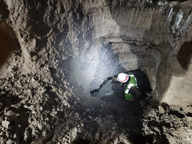 Ryan James, a digging contractor, breaks through into the back of the gravel room for the first time from the new back crosscut in the Cold Regions Research and Engineering Laboratory's Permafrost Tunnel Research Facility in Fox, Alaska. The excavation was part of the phase four expansion of the permafrost tunnel, which added a new 300-foot tunnel and improved 200 feet of the pre-existing tunnel.
