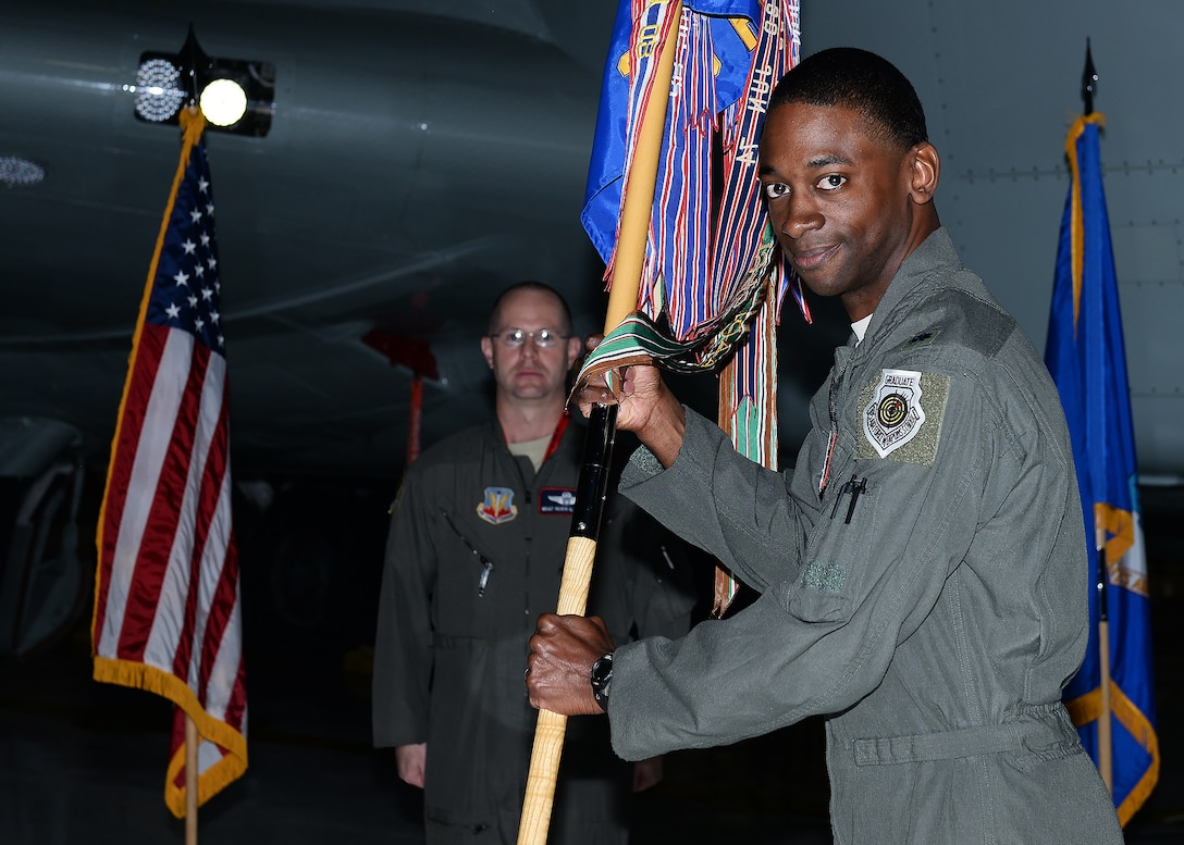 Colonel stands with flag during change of command ceremony