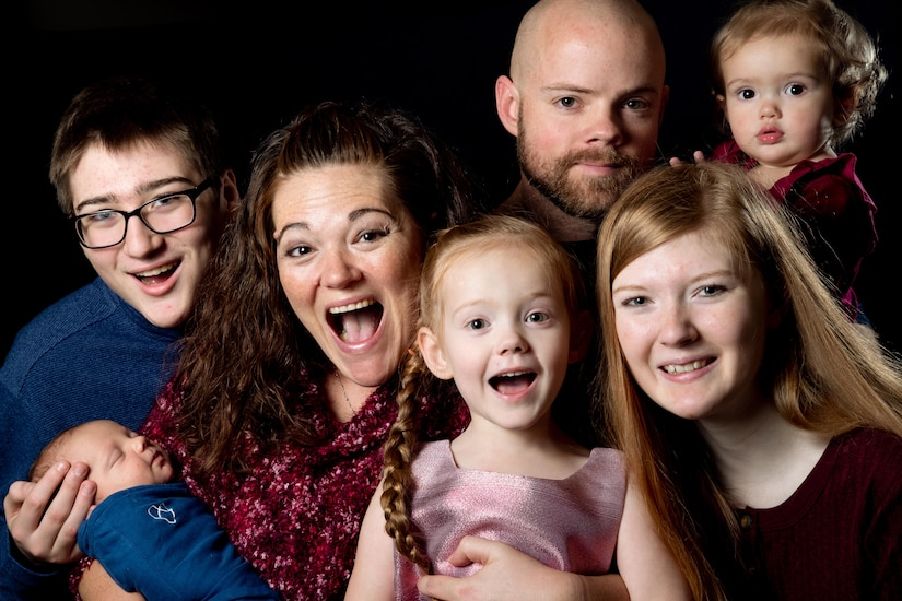 A family of seven smiles for a family portrait.