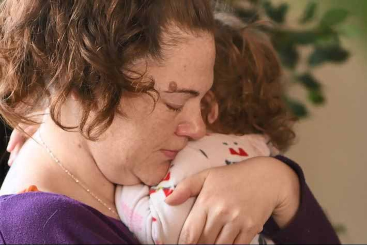 A woman hugs her 1-year-old child