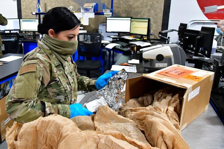 Staff Sgt. Mia Blakley sifting through packaging of a box.