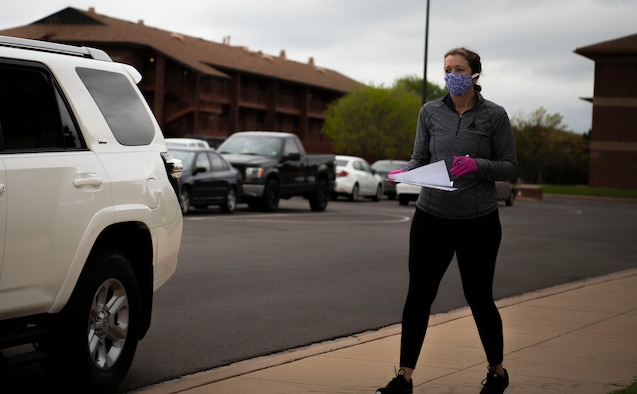 Jennifer Sumangil, Dyess Spouse's Club member, distributes fabric to spouses volunteering to make face-masks at Dyess Air Force Base, Texas, April 11, 2020.