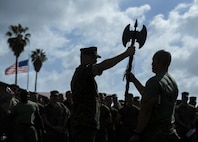 U.S. Marine Corps Sgt. Maj. Ryan W. Meltesen, left, sergeant major of 1st Light Armored Reconnaissance Battalion (1st LAR), 1st Marine Division (1st MARDIV), hands the battle-axe to Capt. Jeshua O. Alston, an infantry officer with 1st LAR, 1st MARDIV, during Warrior Day at Marine Corps Base Camp Pendleton, California, March 13, 2019.