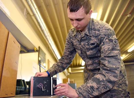 Airman 1st Class Patrick Fitzgerald, 100th Logistics Readiness Squadron flight service center technician, uses an electrostatic dissipative table to inspect an item at RAF Mildenhall, England, April 15, 2020. The flight service Airmen are responsible for the tracking, inspecting, verifying, delivering and picking up all parts from maintenance squadrons on base. (U.S. Air Force photo by Senior Airman Brandon Esau)