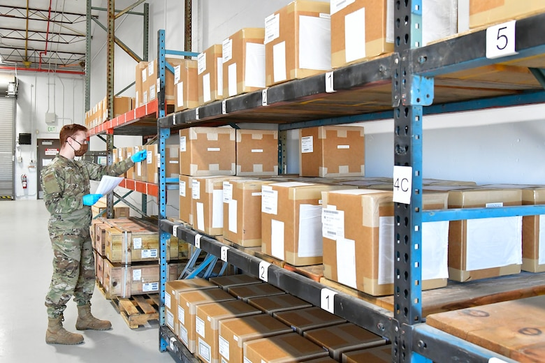 Senior Airman Devon Levesque inspecting boxes on a shelf.