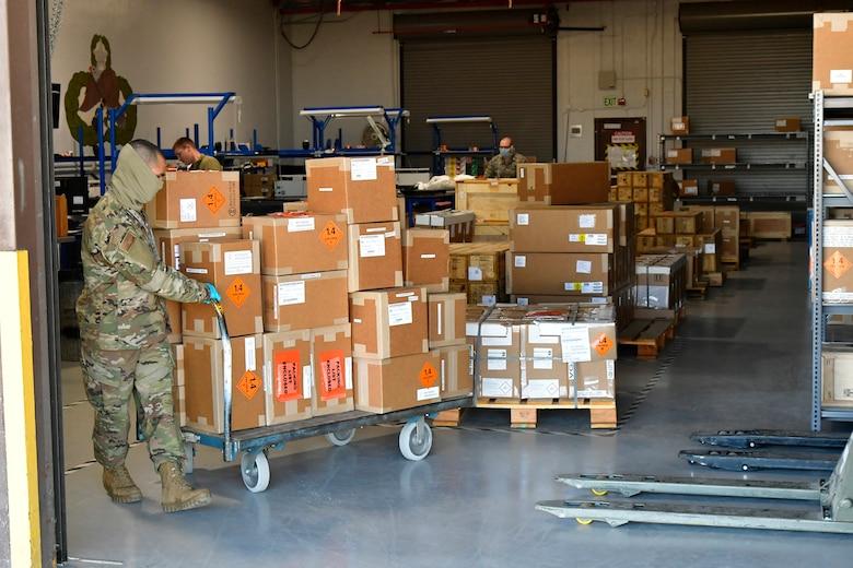 Senior Airman Armando Pena pulling a cart loaded with boxes.