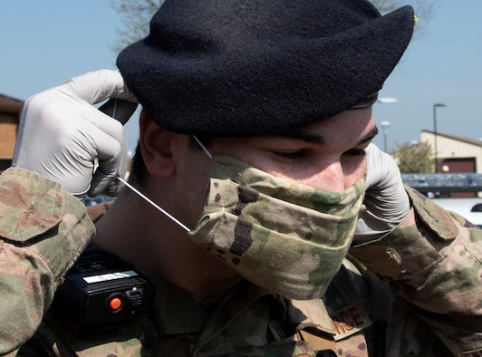 Senior Airman Jeffrey Clark, a 48th Security Forces Squadron response force leader, puts on a protective face mask at Royal Air Force Lakenheath, England, April 16, 2020. The squadron has taken preventative measures to combat the spread of COVID-19 as they continue to protect and defend U.S. Air Forces in Europe's largest fighter wing. (U.S. Air Force photo by Airman 1st Class Jessi Monte)
