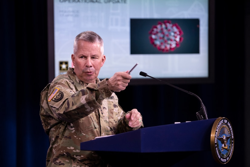 A man in a military uniform stands at a lectern while gesturing with a pen. A graphic of the COVID-19 virus is on a screen in the background.
