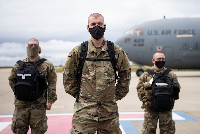Airmen from Basic Military Training stand in formation on the flightline after getting off a C-17 April 17, 2020, at Vandenberg Air Force Base, Calif. Typically, members leaving BMT from Joint Base San Antonio-Lackland, Texas, travel on commercial aircraft to get to their technical school locations. However, under current COVID-19 circumstances, the Airmen are flown on military aircraft to designated bases and transported to their tech school locations by bus. The students went through a 14-day quarantine at BMT prior to flying. (U.S. Air Force photo by Senior Airman Aubree Owens)
