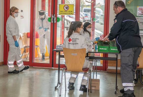 Bitburg-Prüm County Deutsches Rotes Kreuz volunteers, collect and process COVID-19 nasal swabs at a COVID-19 testing facility set up at the former Bitburg Air Base Commissary, Bitburg, Germany, April 10, 2020. Partnering with host nation colleagues increased crosstalk between 52nd Medical Group professionals, and opened new ways of thinking and approaching shared challenges. (U.S. Air Force photo by Airman 1st Class Alex Miller)