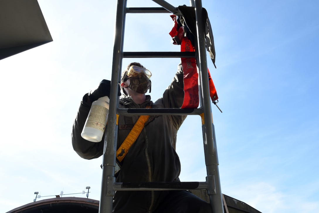 A 493rd Aircraft Maintenance Unit crew chief cleans a ladder to prevent the spread of COVID-19 at Royal Air Force Lakenheath, England, April 15, 2020. The task requires everything inside the cockpit to be sanitized, to include any tool, button or switch the aircrew may have come in contact with during their flight. (U.S. Air Force photo by Airman 1st Class Rhonda Smith)
