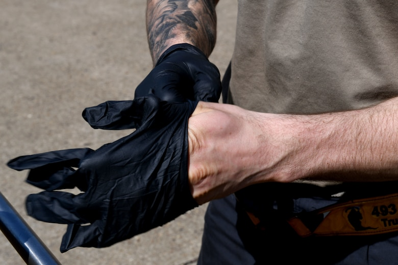 A 493rd Aircraft Maintenance Unit crew chief puts on protective gloves in preparation to sanitize an F-15C Eagle cockpit to prevent the spread of COVID-19 at Royal Air Force Lakenheath, England, April 15, 2020. Crew chiefs are required to take safety precautions to help protect themselves and other aircrew who may come in contact with the aircraft. (U.S. Air Force photo by Senior Airman Christopher S. Sparks)