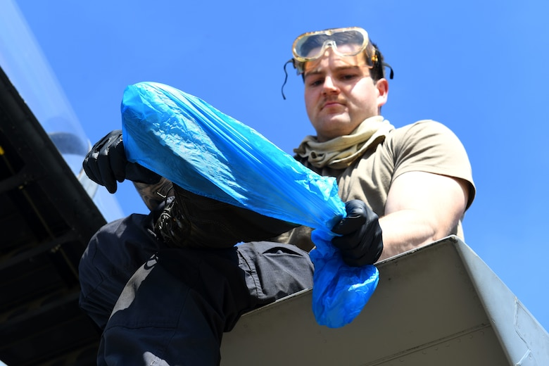 A 493rd Aircraft Maintenance Unit crew chief dons boot-covers as a precaution before sanitizing an F-15C Eagle cockpit to prevent the spread of COVID-19 at Royal Air Force Lakenheath, England, April 15, 2020. Personal protective equipment for cleaning includes wearing gloves, goggles and foot protection while using a sanitizing solution spray and cloth. Afterwards, each item is properly disposed of before the Airman returns to the squadron. (U.S. Air Force photo by Senior Airman Christopher S. Sparks)