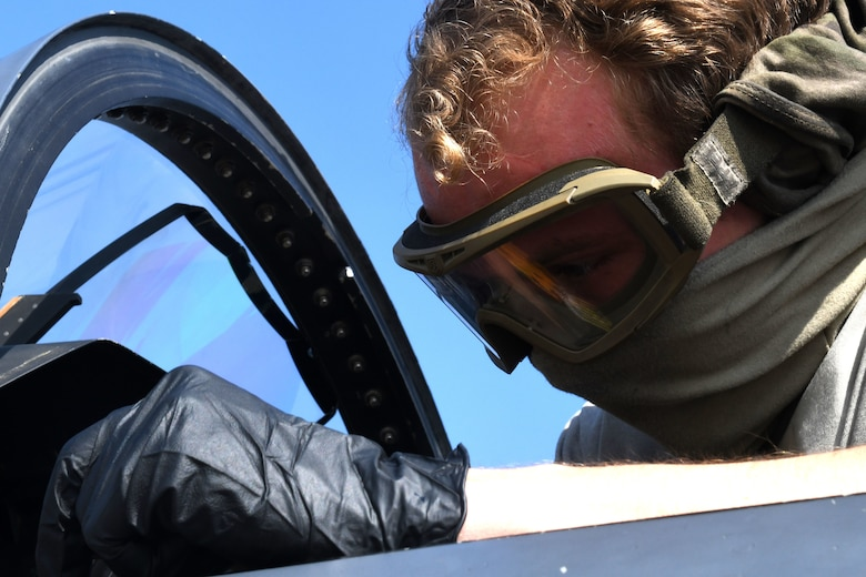 A 494th Aircraft Maintenance Unit crew chief cleans the cockpit of an F-15E Strike Eagle to prevent the spread of COVID-19 at Royal Air Force Lakenheath, England, April 16, 2020. Crew chiefs are required to take safety precautions to help protect themselves and other aircrew who may come in contact with the aircraft. (U.S. Air Force photo by Senior Airman Christopher S. Sparks)