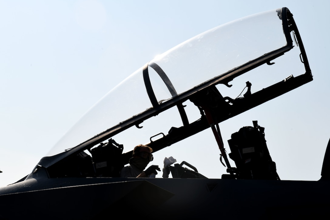 A 494th Aircraft Maintenance Unit crew chief sanitizes the cockpit of an F-15E Strike Eagle to prevent the spread of COVID-19 at Royal Air Force Lakenheath, England, April 16, 2020. Personal protective equipment for cleaning includes wearing gloves, goggles and foot protection while using a sanitizing solution spray and cloth. Afterwards, each item is properly disposed of before the Airman returns to the squadron. (U.S. Air Force photo by Senior Airman Christopher S. Sparks)