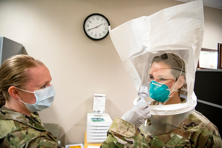 U.S. Air Force Tech Sgt. Kristen Nickerson, left, 423d Medical Squadron NCO in charge of bio-environmental engineering, conducts a qualitative fit test on a N95 mask for Staff Sgt. Jennalyse Adam, 423d MDS dental assistant, at RAF Alconbury, England April 14, 2020. The 423d MDS were conducting fit tests of the N95 mask to ensure personnel are safe to continue to treat patients who may have contracted the novel coronavirus. (U.S. Air Force photo by Senior Airman Eugene Oliver)