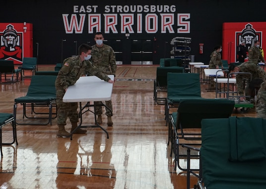 Soldiers from the Pennsylvania National Guard help unload supplies from a Pennsylvania Department of Health trailer at East Stroudsburg University's Koehler Fieldhouse on April 14, 2020.
