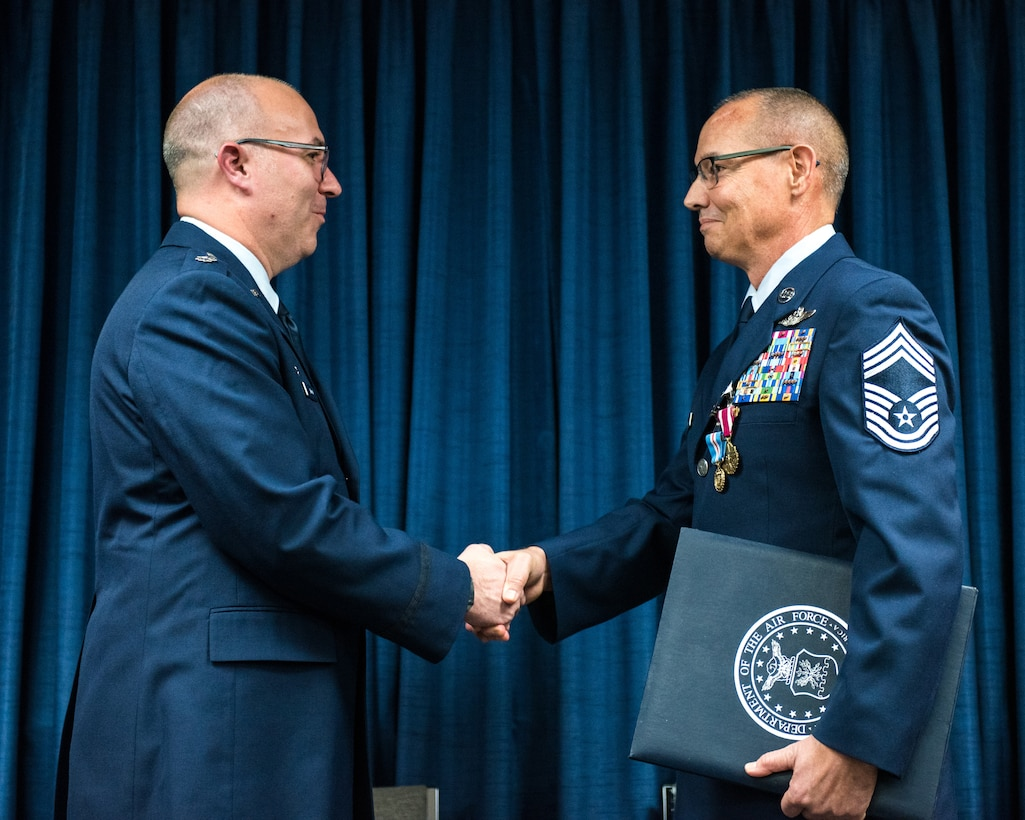 Lt. Col. Randall Hood (left), commander of the 123rd Operations Support Squadron, presents Chief Master Sgt. Jeffrey Brown, a loadmaster supervisor in the 165th Airlift Squadron, with a certificate of retirement during Brown's retirement ceremony at the Kentucky Air National Guard Base in Louisville, Ky., Dec. 7, 2019. (U.S. Air National Guard photo by Senior Airman Chloe Ochs)