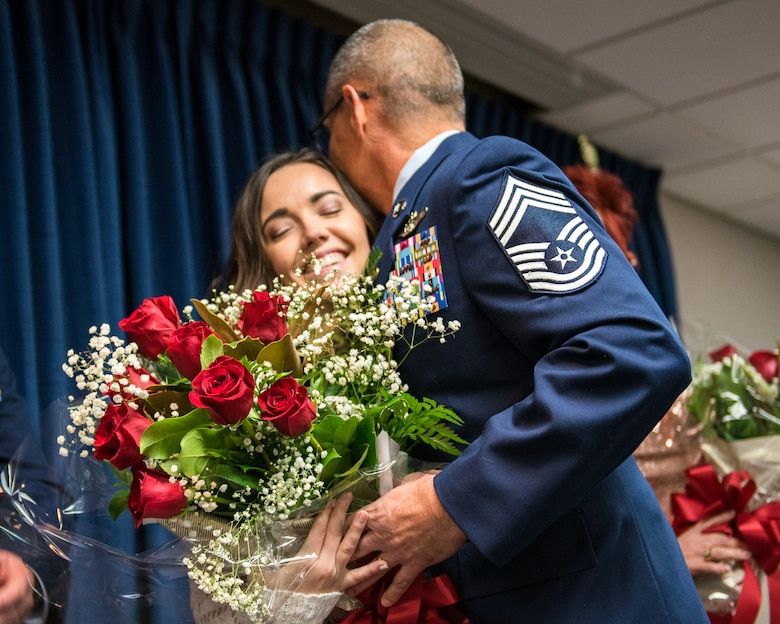 Chief Master Sgt. Jeffrey Brown, a loadmaster supervisor with the 165th Airlift Squadron, presents his daughter with a bouquet of roses during his ceremony at the Kentucky Air National Guard Base in Louisville, Ky., Dec. 7, 2019. (U.S. Air National Guard photo by Senior Airman Chloe Ochs)