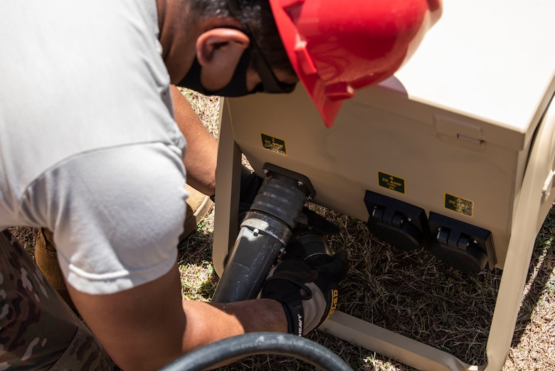 An Airman from the 554th RED HORSE Squadron readies a generator for a temporary warehouse unit as part of the construction of an Expeditionary Medical Support System facility April 13, 2020, at U.S. Naval Hospital Guam.