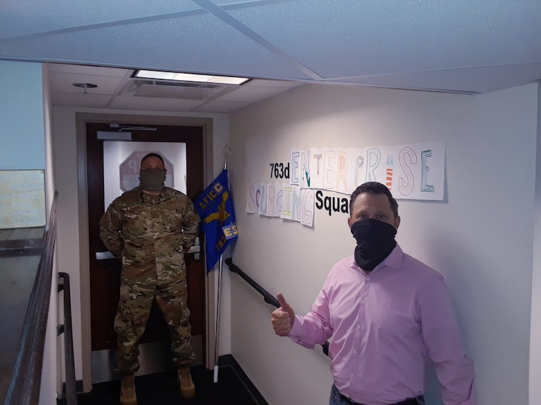 Greg English and Maj. Jimmy Thompson, director and deputy director respectively, of the newly designated 763rd Enterprise Sourcing Squadron, pose with new homemade signage, displaying true agility during the COVID-19 pandemic.