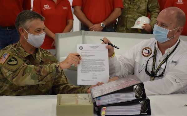 Col. Andrew Kelly, commander of the Jacksonville District of the U.S. Army Corps of Engineers, hands a letter certifying the completion of the Alternate Care Facility the district built in the Miami Convention Center to Kevin Guthrie, Deputy Director of the Florida Division of Emergency Management. The facility provides 450 beds, 50 of them intensive care unit beds, gives the state of Florida medical providers and state emergency managers flexibility as they prepare for a COVID-19 based surge at local and regional medical facilities. Initially, the facility was to be completed by April 27, but the deadline was moved to April 20 after a meeting with the Florida governor identified an expedited need. Even with the shortened deadline, the Corps of Engineers delivered the site early, with the contractor completing construction April 18 and the Corps signing over the facility to the state on April 19.