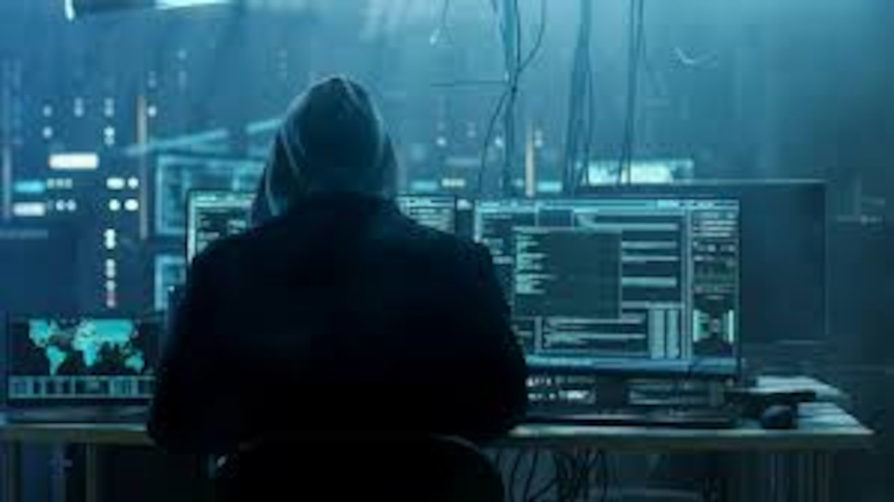 The view from behind a hooded figure, who is looking at several computer screens in a dingy room.