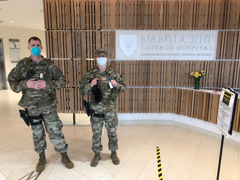 Two security forces defenders wearing face masks stand at the entrance to Nantucket Cottage Hospital