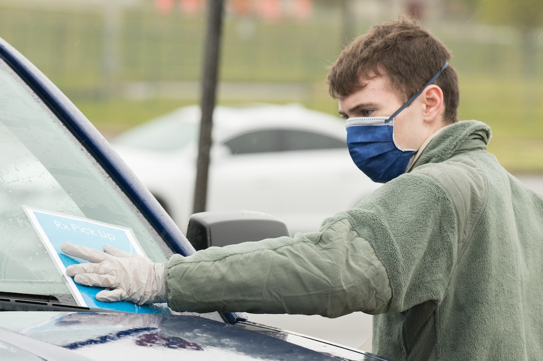 Airman 1st Class Jacob Goucher, 436th Aircraft Maintenance Squadron C-5M apprentice, places a number card on a vehicle windshield at a curbside pharmacy, April 18, 2020, at Dover Air Force Base, Delaware. The curbside project offers full pharmacy services including new prescriptions and refills, allowing Team Dover to access prescriptions and maintain social distancing. (U.S. Air Force photo by Mauricio Campino)