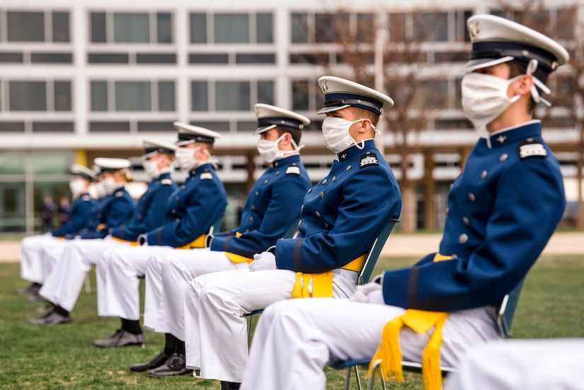 U.S. Air Force Academy cadets wearing masks sit in a row on a field.