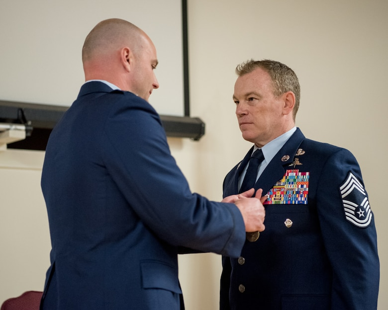 Chief Master Sgt. Aaron May (right), the outgoing chief enlisted manager for the 123rd Special Tactics Squadron, is pinned with the Meritorious Service Medal by Capt. Russ LeMay, Norse Troop officer in charge for the 123rd Special Tactics Squadron, during May's retirement ceremony at the Kentucky Air National Guard Base in Louisville, Ky., on Dec. 7, 2019. May is retiring after more than 26 years of service to the Kentucky Air National Guard and U.S. Air Force. (U.S. Air National Guard photo by Staff Sgt. Joshua Horton)