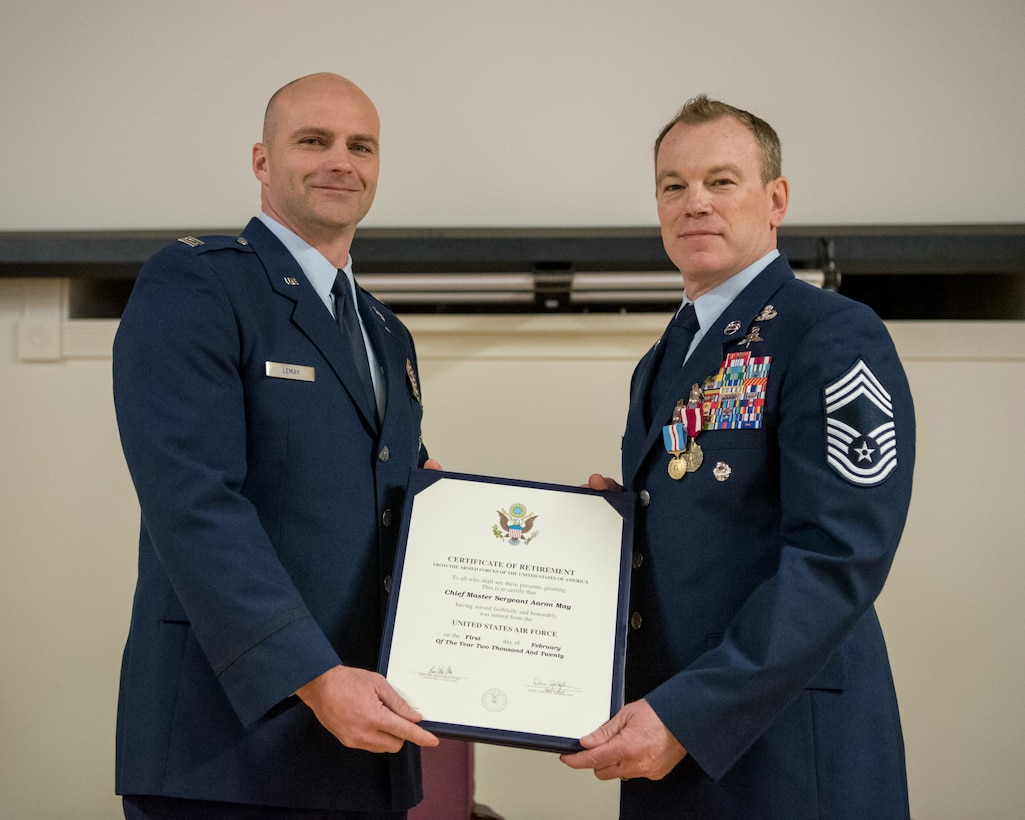 Chief Master Sgt. Aaron May (right), the outgoing chief enlisted manager for the 123rd Special Tactics Squadron, receives his certificate of retirement from Capt. Russ LeMay, Norse Troop officer in charge for the 123rd Special Tactics Squadron, during May's retirement ceremony at the Kentucky Air National Guard Base in Louisville, Ky., on Dec. 7, 2019. May is retiring after more than 26 years of service to the Kentucky Air National Guard and U.S. Air Force. (U.S. Air National Guard photo by Staff Sgt. Joshua Horton)