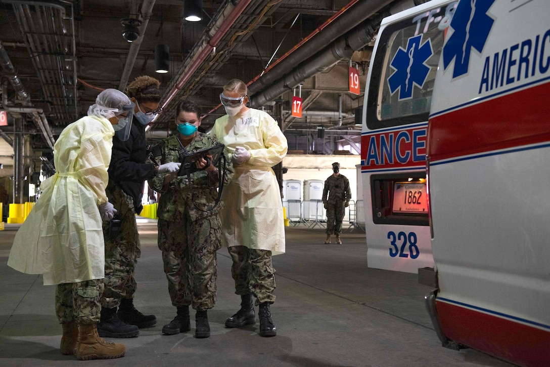 Four sailors dressed in protective gear consult an electronic device as they stand by the open back door of an ambulance.