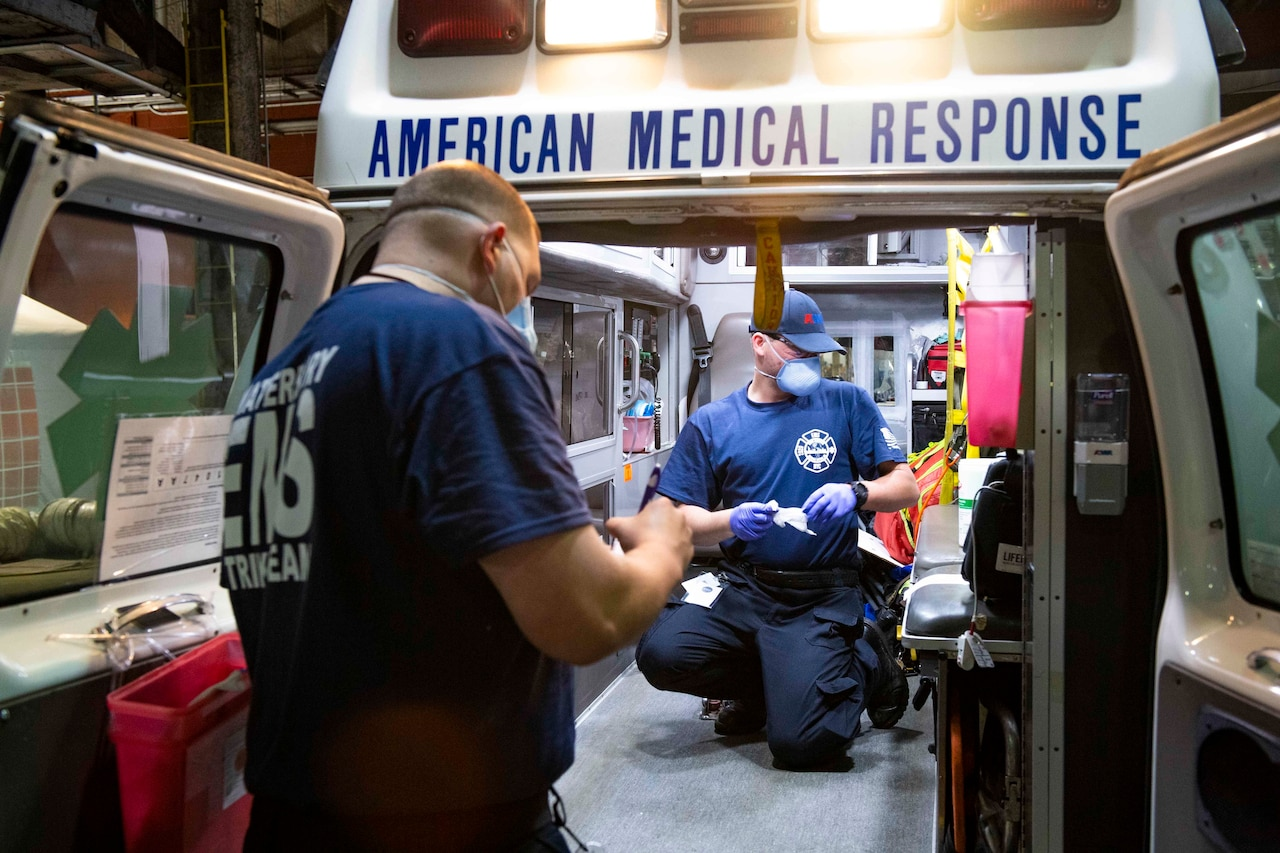 Medical technicians wearing protective gear sanitize the inside of an ambulance.