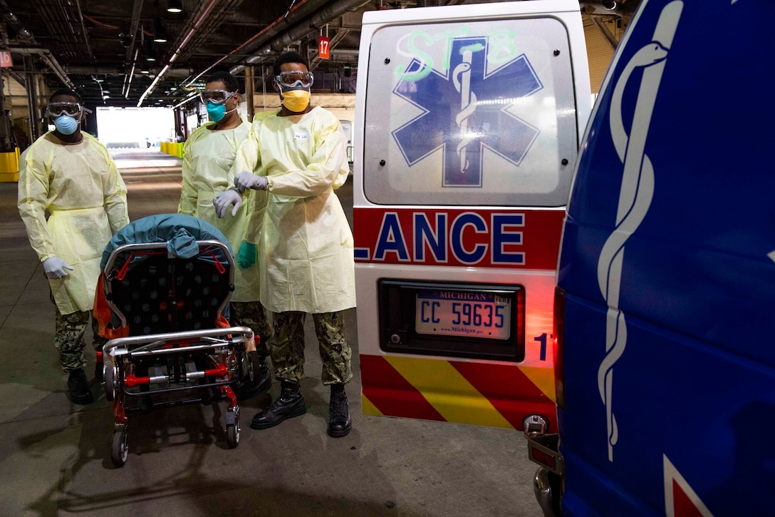 Sailors wearing protective gear stand by the open back door of an ambulance.