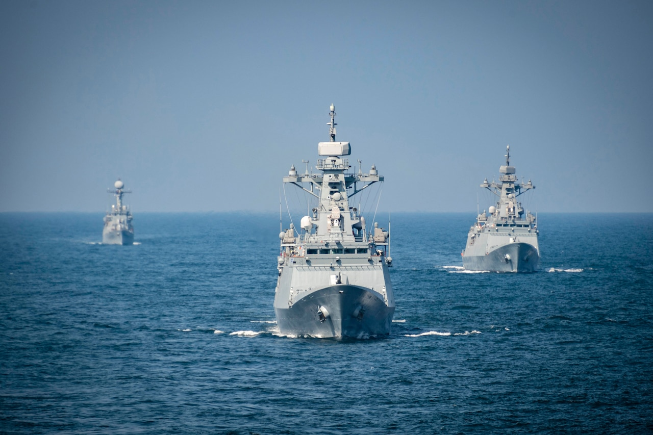 Three ships sail near each other in open water.
