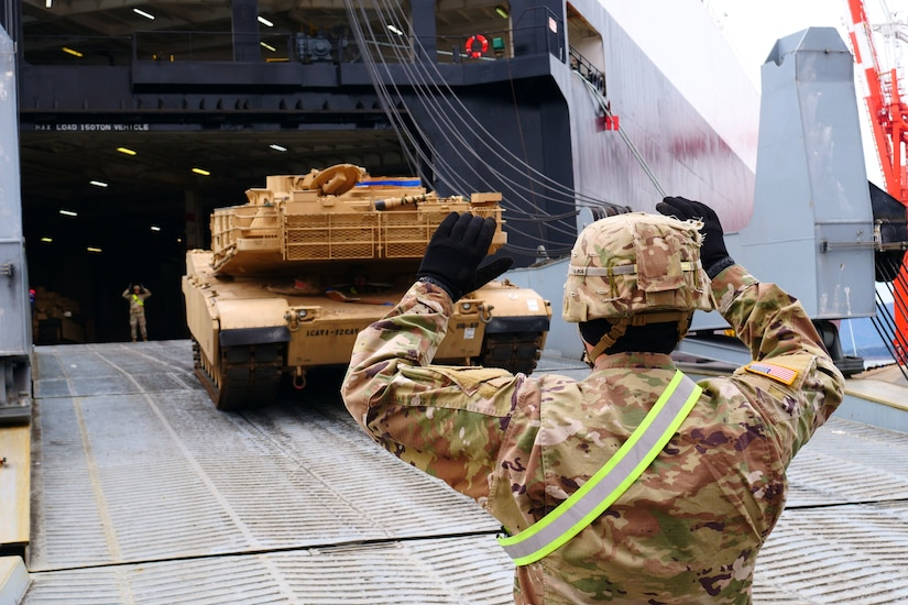 A soldier guides a tank onto a ship