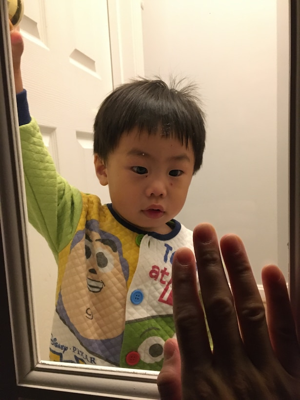 During quarantine, Master Sgt. Matthew Alejandro, 844th Communications Squadron executive team member, holds his hand up to the glass pane of his office door as his son, Maxwell, 2, looks on. Undated photo. (Air Force photo/Master Sgt. Matthew Alejandro)