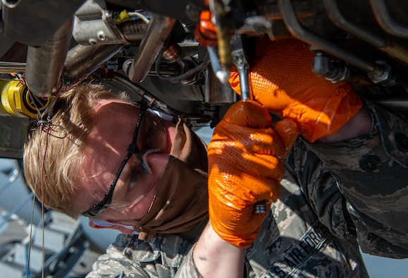 Airman 1st Class Ian Cernetich, 62nd Maintenance Squadron hydraulics apprentice, removes a hydraulic pump from the engine of a C-17 Globemaster III at Joint Base Lewis-McChord, Wash., April 14, 2020. The 62nd Airlift Wing has initiated a minimal manning posture and since maintenance Airmen are mission essential, they must take precautions such as wearing protective masks to stay healthy while working on aircraft. (U.S. Air Force photo by Senior Airman Tryphena Mayhugh)