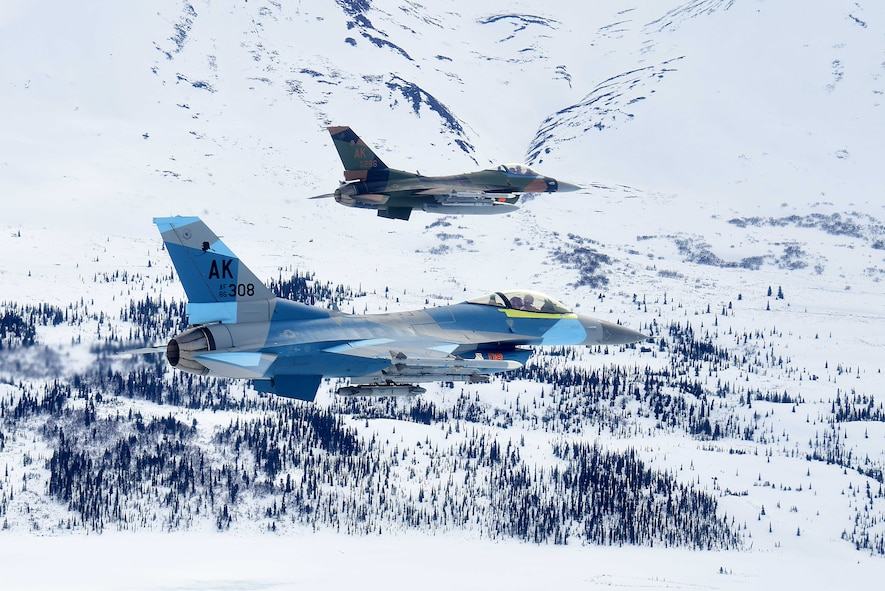 Two U.S. Air Force F-16 Fighting Falcons assigned to the 18th Aggressor Squadron fly over the Joint Pacific Alaska Range Complex during a training sortie with F-22 Raptors stationed at Joint Base Elmendorf-Richardson in Anchorage, Alaska, April 17, 2020.