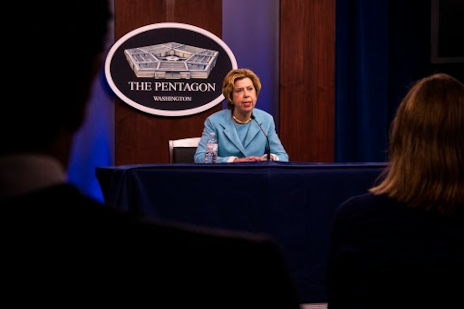 """Woman seated at a table with a microphone speaks. There is a sign in the background stating that it is """"The Pentagon."""""""