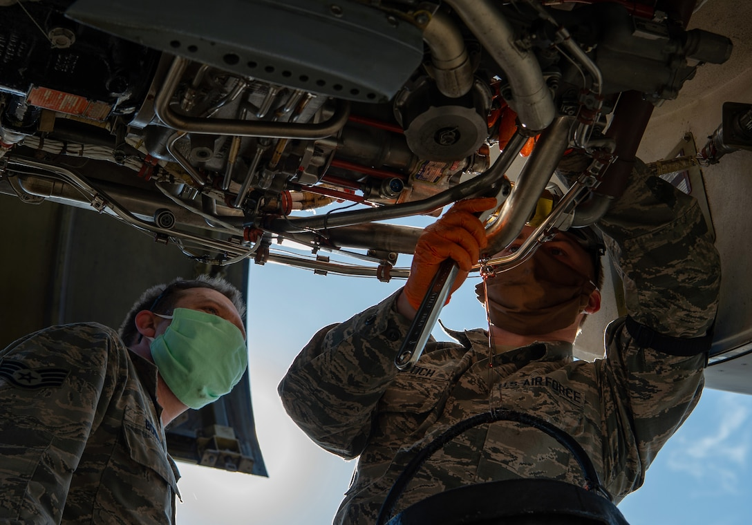 Staff Sgt. Christopher Bowen, 62nd Maintenance Squadron (MXS) hydraulics technician, supervises while Airman 1st Class Ian Cernetich, 62nd MXS hydraulics apprentice, works to remove a hydraulic pump from the engine of a C-17 Globemaster III at Joint Base Lewis-McChord, Wash., April 14, 2020. Both Airmen are wearing protective masks to help stop the spread of COVID-19 while they work. (U.S. Air Force photo by Senior Airman Tryphena Mayhugh)