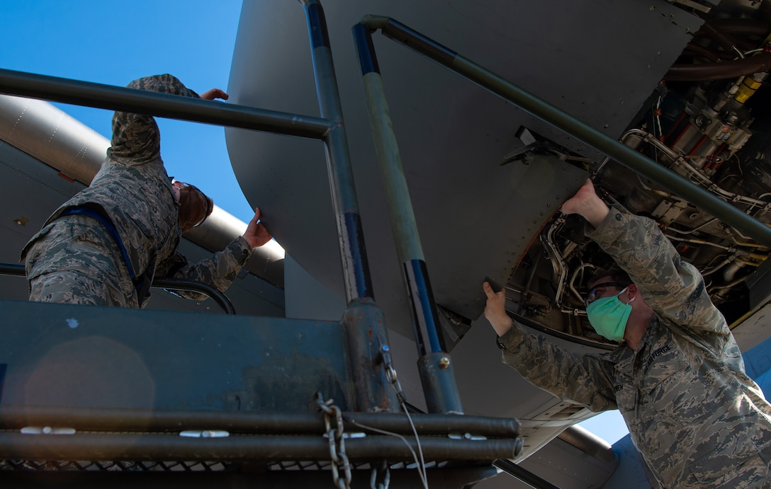 Staff Sgt. Christopher Bowen, 62nd Maintenance Squadron (MXS) hydraulics technician, right, and Airman 1st Class Ian Cernetich, 62nd MXS hydraulics apprentice, open the panel covering the engine of a C-17 Globemaster III at Joint Base Lewis-McChord, Wash., April 14, 2020. Maintenance Airmen are mission essential and cannot be sent home to maintain social distancing during the COVID-19 pandemic, so they must take precautions such as wearing protective masks to stay healthy while continuing to execute their mission. (U.S. Air Force photo by Senior Airman Tryphena Mayhugh)