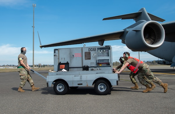 Tech. Sgt. Veryon Moore, 62nd Aircraft Maintenance Squadron (AMXS) integrated flight control systems craftsman; Senior Airman Tyler DiNoto, 62nd AMXS integrated flight control systems journeyman, front right; and Staff Sgt. Bertrand Foley, 62nd AMXS communication, navigation and mission systems craftsman, move a generator away from a C-17 Globemaster III at Joint Base Lewis-McChord, Wash., April 14, 2020. Airmen wear protective masks to protect themselves and others from the spread of COVID-19 while continuing to perform their duties. (U.S. Air Force photo by Senior Airman Tryphena Mayhugh)