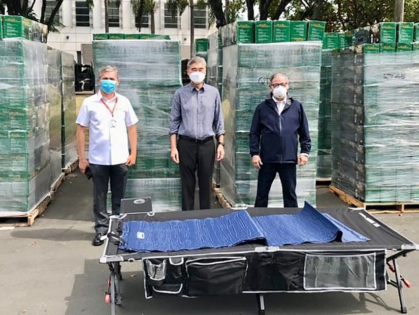 Government leaders pose in front of boxes of cots.